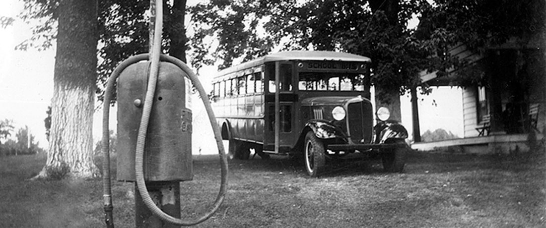 A vintage photo of an old school bus with an old gas pump in the foreground.