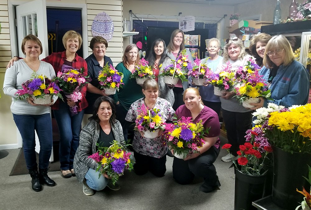 Group of ladies holding flower bouquets they designed during a night out event.