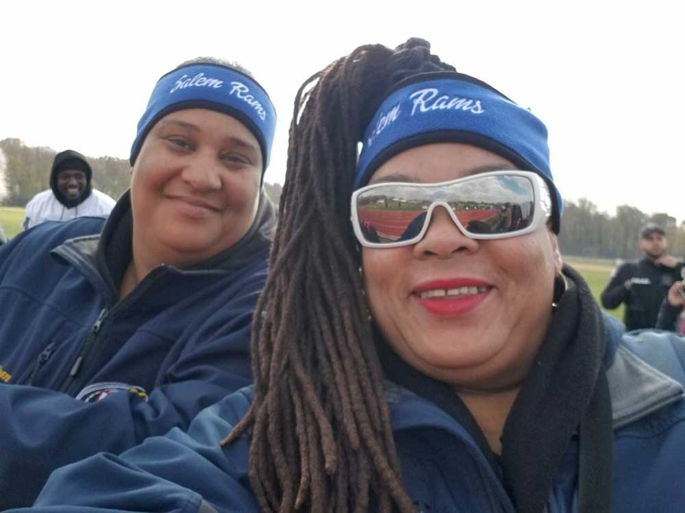 Bus driver and another person wearng Salem Rams headbands at a game.