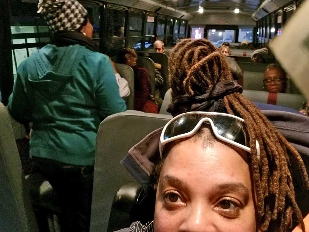 Bus driver selfie with children behind her on the bus.