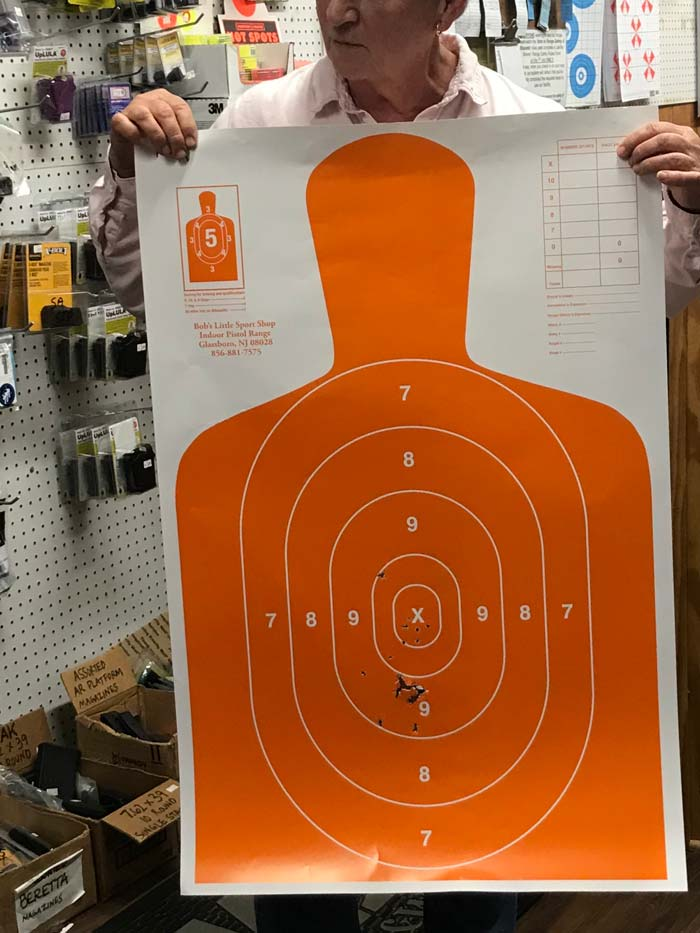 Man holds up paper target during Shoot 'em Up Night