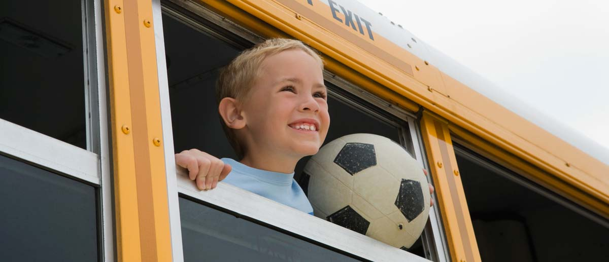 Smiling boy with a soccer ball looking out of open bus window.