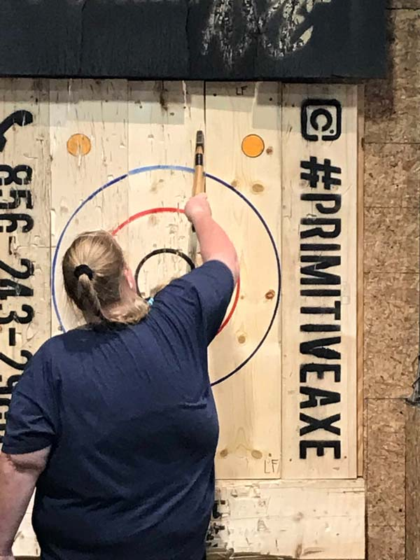 Woman pulling axe out of board during Axe-travaganza event