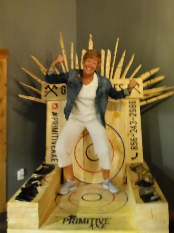 Chloe Williams standing on top of a wood throne at Axe-travaganza