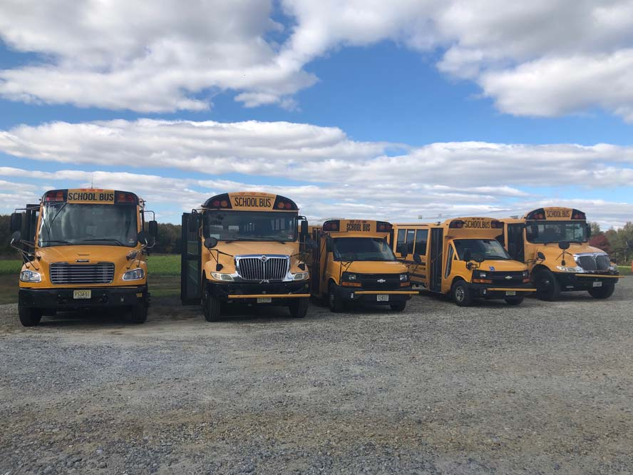 Five different styles of school bus lined up in lot under a blue sky wth clouds.