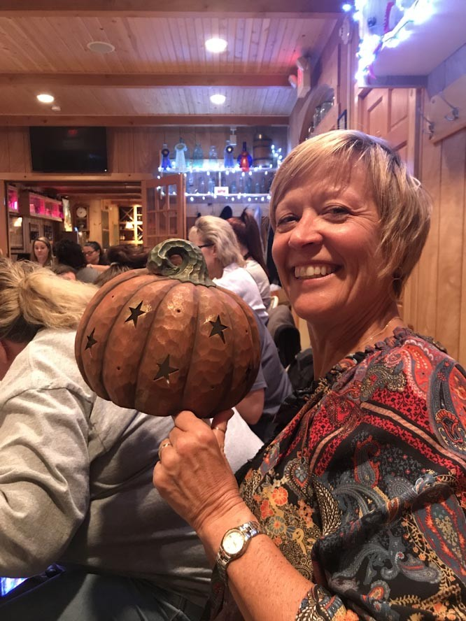 Lady holds a ceramic pumpkin she decorated