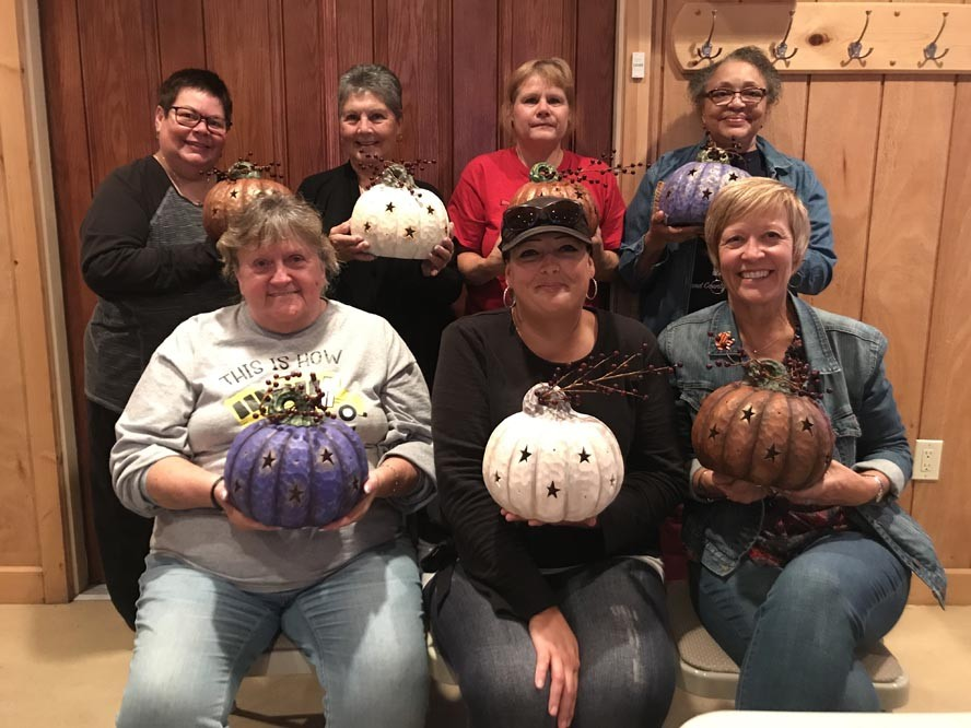 Group of ladies holding decorated ceramic pumpkins as part of a Fun Night Out